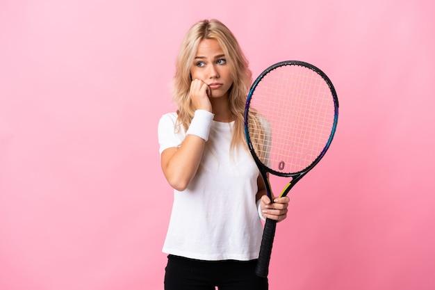 Молодая русская женщина играет в теннис изолирована на фиолетовом с усталым и скучающим выражением лица