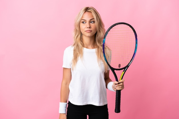 Young russian woman playing tennis isolated on purple having doubts while looking side