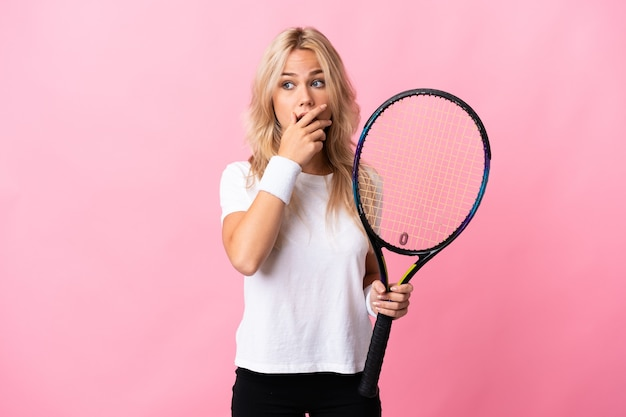 Young russian woman playing tennis isolated on purple wall doing surprise gesture while looking to the side