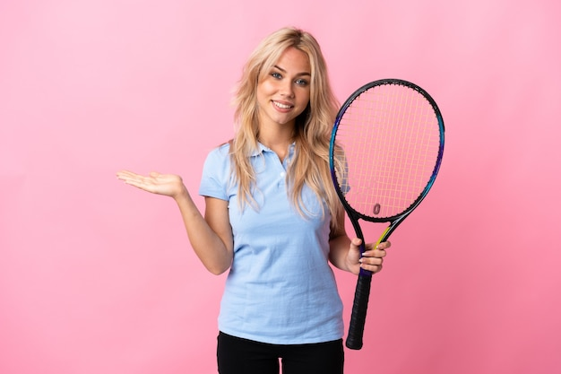 Young russian woman playing tennis isolated on purple wall holding copyspace imaginary on the palm to insert an ad