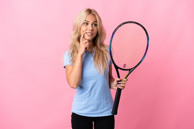 Young russian woman playing tennis isolated on purple wall thinking an idea while looking up
