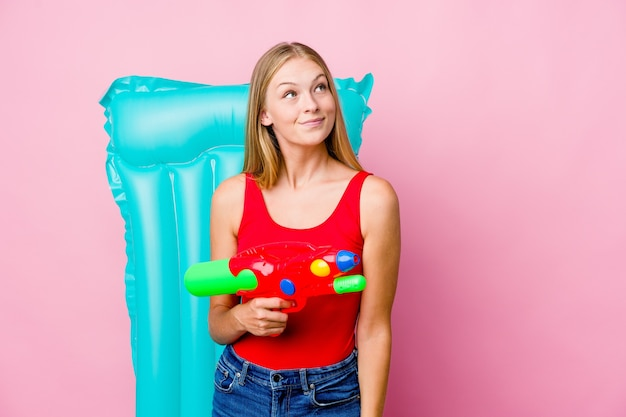 目標と目的を達成することを夢見ているエアマットレスと水鉄砲で遊んでいる若いロシアの女性