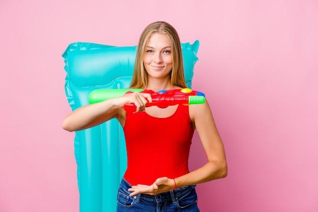 Молодая русская женщина играет с водяным пистолетом с надувным матрасом, что-то держит обеими руками, презентация продукта.