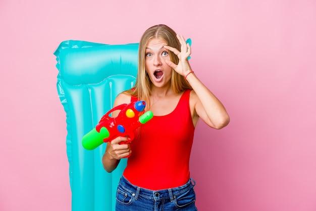 Молодая русская женщина играет с водяным пистолетом на надувном матрасе, держа глаза открытыми, чтобы найти возможность успеха.