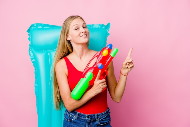 コピースペースに人差し指で指しているエアマットレスと水鉄砲で遊んで、興奮と欲望を表現している若いロシアの女性。