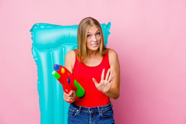 嫌悪感のジェスチャーを示している誰かを拒否するエアマットレスと水鉄砲で遊んでいる若いロシアの女性。