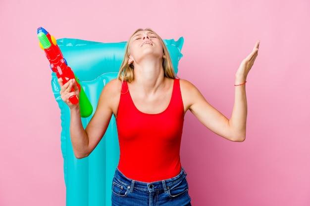 Молодая русская женщина играет с водяным пистолетом на надувном матрасе, кричит в небо, глядя вверх, разочарованная