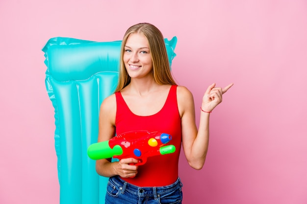 笑顔で脇を向いて、空白のスペースで何かを見せて、エアマットレスと水鉄砲で遊んでいる若いロシアの女性。