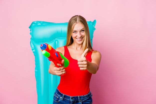 Молодая русская женщина играет с водяным пистолетом на надувном матрасе с большими пальцами руки вверх, приветствует что-то