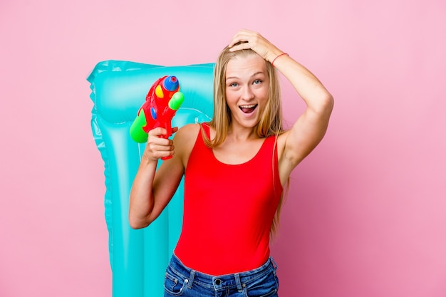 Young russian woman playing with a water gun with an air mattress laughs joyfully keeping hands on head. happiness concept.