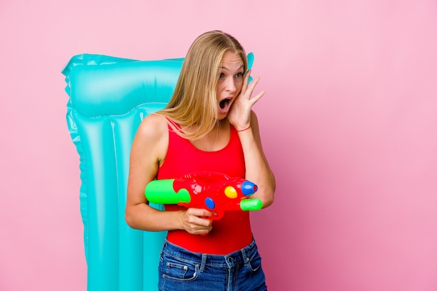 Young russian woman playing with a water gun with an air mattress shouts loud, keeps eyes opened and hands tense.