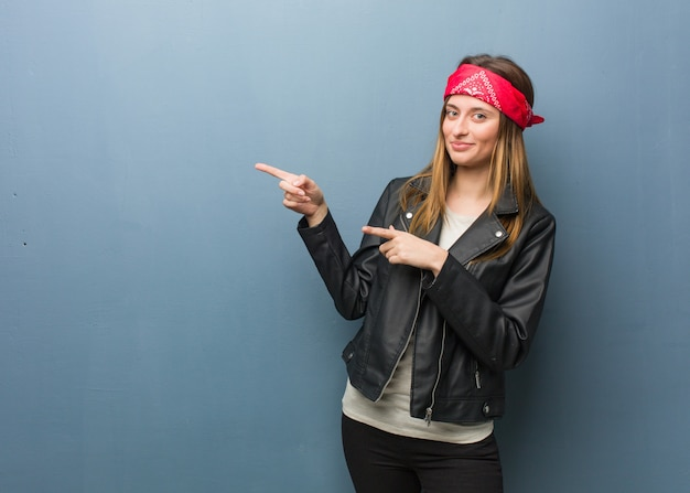 Young russian woman pointing to the side with finger