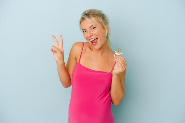 青の背景に分離されたおしゃぶりを持って妊娠中の若いロシア人女性は、指で平和のシンボルを喜んで気楽に示しています。