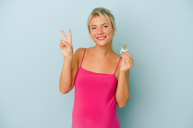 Young russian woman pregnant holding a pacifier isolated on blue background showing number two with fingers.