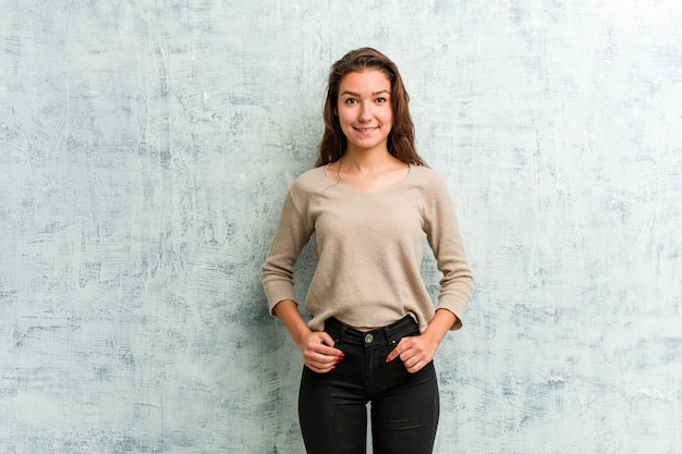 Young russian woman smiling against a grunge wall