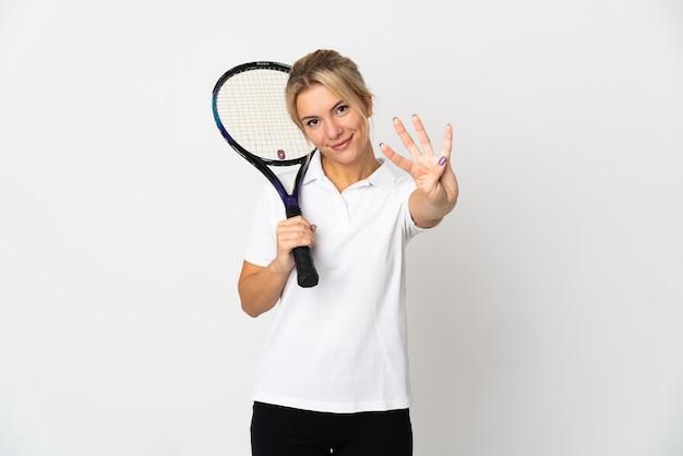 Молодая русская теннисистка изолирована на белом фоне счастлива и считает четыре пальцами
