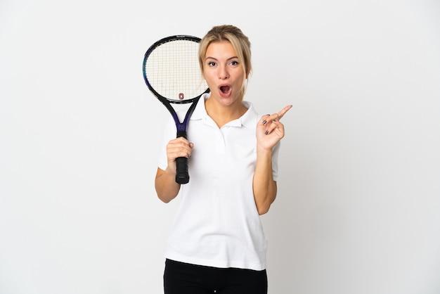 Молодая русская теннисистка изолирована на белом фоне, намереваясь реализовать решение, подняв палец вверх