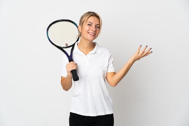 Молодая россиянка-теннисистка изолирована на белой стене, протягивая руки в сторону для приглашения приехать