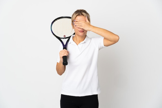 Young russian woman tennis player isolated on white background covering eyes by hands. do not want to see something
