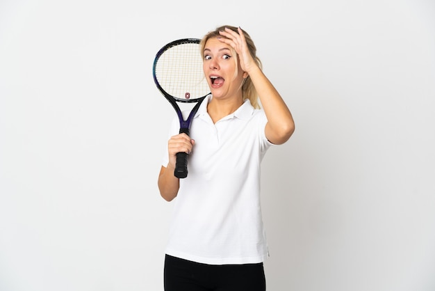 Young russian woman tennis player isolated on white background doing surprise gesture while looking to the side