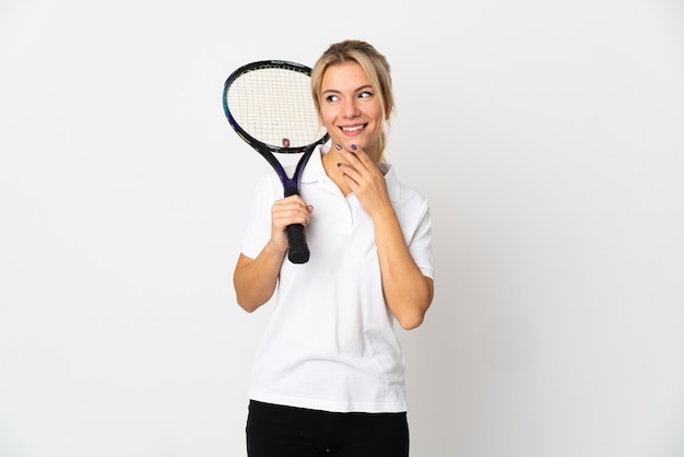 Young russian woman tennis player isolated on white background looking up while smiling