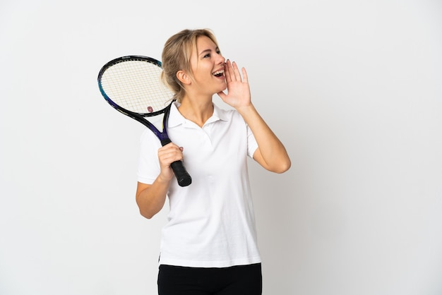 Young russian woman tennis player isolated on white background shouting with mouth wide open to the side