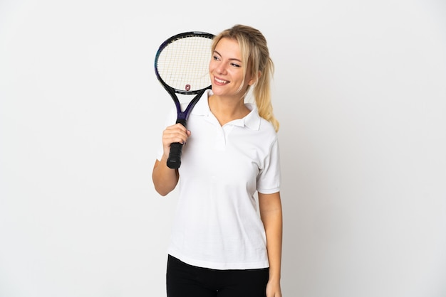 Young russian woman tennis player isolated on white looking to the side and smiling