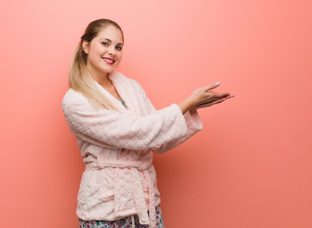 Young russian woman wearing pajama holding something with hands