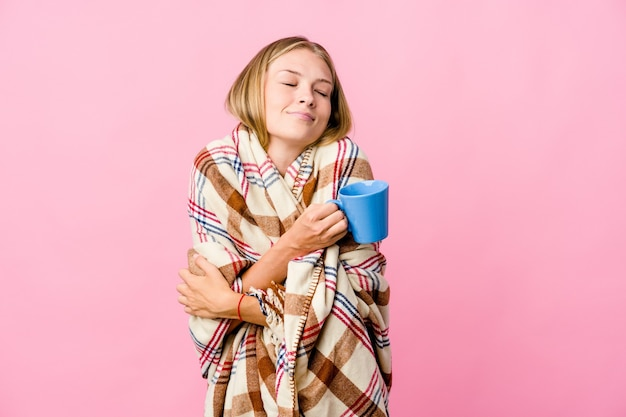 Young russian woman wrapped in a blanket drinking coffee hugs, smiling carefree and happy.