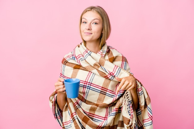 Young russian woman wrapped in a blanket drinking coffee points down with fingers, positive feeling