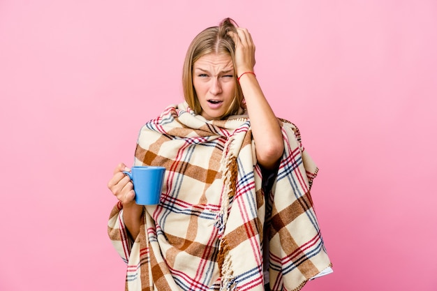 Young russian woman wrapped in a blanket drinking coffee tired and very sleepy keeping hand on head.
