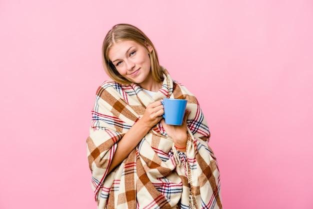 コーヒーを飲む毛布に包まれた若いロシア人女性は、手のひらを胸に押し付けて、優しい表情をしています。愛の概念。