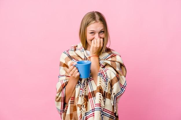 젊은 러시아 여자는 뭔가에 대해 웃고, 손으로 입을 덮고 커피를 마시는 담요에 싸여있다.