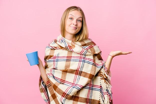 커피를 마시는 담요에 싸여있는 젊은 러시아 여성은 팔로 규모를 만들고 행복하고 자신감을 느낍니다.