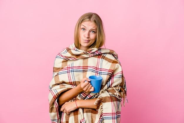 Молодая русская женщина, завернутая в одеяло, пьет кофе недовольно, глядя в камеру с саркастическим выражением лица.