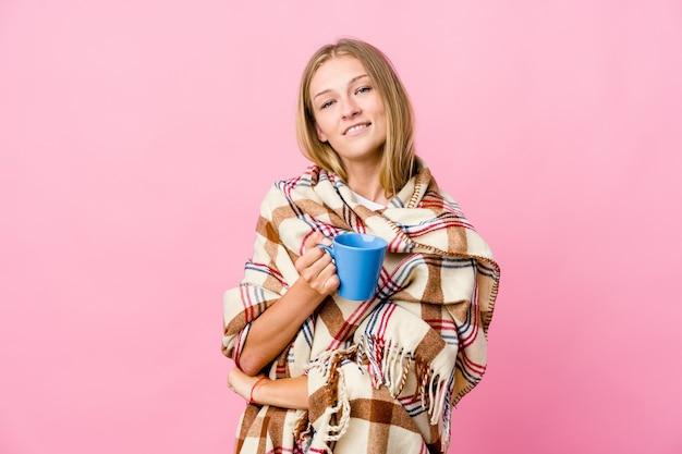 Молодая русская женщина, завернутая в одеяло, пьет кофе, чувствует себя уверенно, решительно скрестив руки