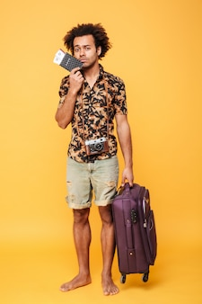 Young sad african man holding passport and suitcase.