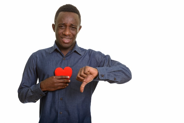 Young sad african man holding red heart on chest