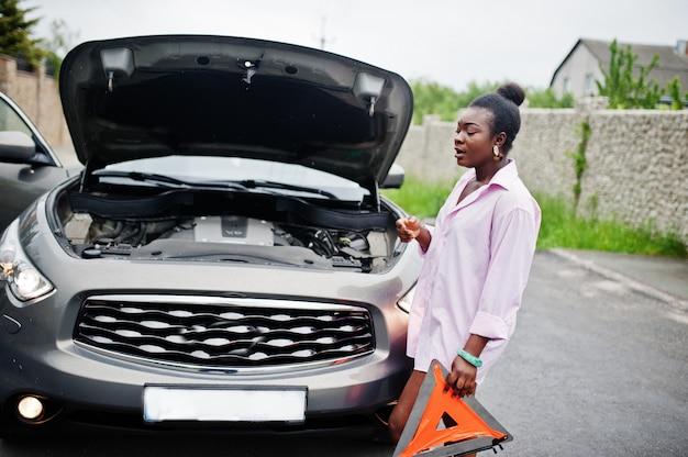 ポップなフードが付いている車に対して緊急の三角形で若い悲しいアフリカ女性スタンド