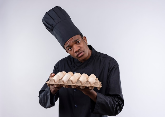 Young sad afro-american cook in chef uniform holds batch of eggs isolated on white wall