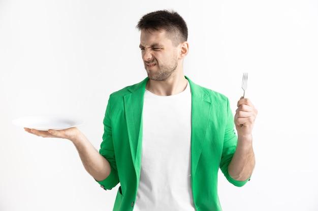 空の皿と灰色の背景で隔離のフォークを保持している若い悲しい魅力的な白人の男。スペースをコピーしてモックアップします。空白のテンプレートの背景。拒否、拒否の概念
