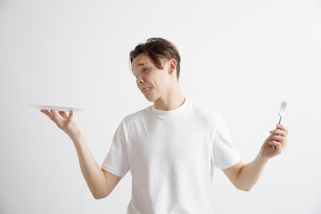 Giovane ragazzo caucasico attraente triste che tiene piatto vuoto e forchetta isolato su sfondo grigio. copia spazio e simula. sfondo modello vuoto. rifiutare