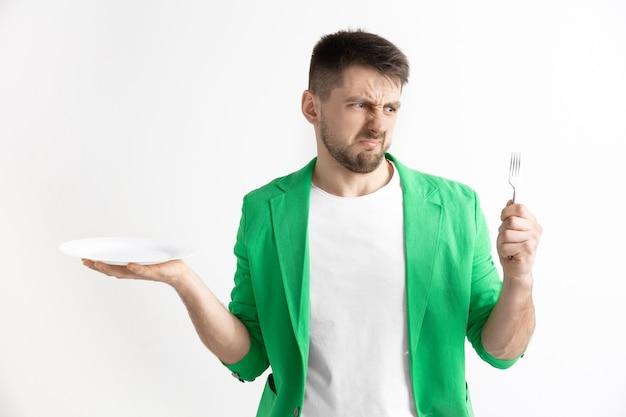 Молодой грустный привлекательный парень, держащий пустое блюдо и вилку, изолированные на серой стене.