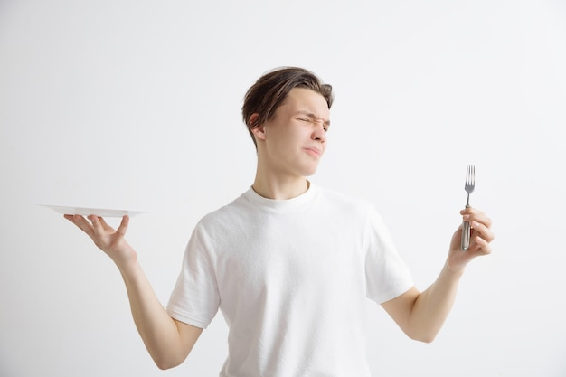 Young sad attractive guy holding empty dish and fork isolated on grey wall.