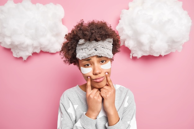 Young sad curly woman forces smile keeps fingers near corners of lips looks unhappily at camera wears sleepmask pajama has sleepy expression as awakes early in morning stands indoor feels upset