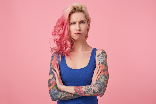 Young sad frowning beauty woman with pink hair, stands with crossed arms, looks displeased, wears a blue shirt. people and emotion concept.