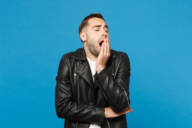 Young sad frustrated worried unshaven man in black jacket white t-shirt looking camera isolated on blue wall background studio portrait. people sincere emotions lifestyle concept. mock up copy space.