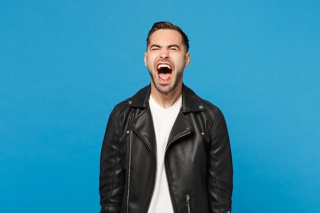 Молодой грустный разочарованный обеспокоенный небритый мужчина в черной куртке, белой футболке, поднимает голову, изолированную на синем стенном фоне студийного портрета. концепция образа жизни искренние эмоции людей. копируйте пространство для копирования.