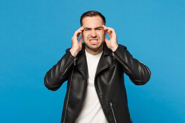 Молодой грустный разочарованный обеспокоенный небритый мужчина в черной куртке, белой футболке, глядя в камеру, изолирован на синем стенном фоне студийного портрета. концепция образа жизни искренние эмоции людей. копируйте пространство для копирования.