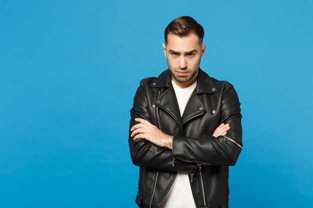 青い壁の背景スタジオの肖像画に分離されたカメラを探している黒いジャケット白いtシャツの若い悲しい欲求不満の心配無精ひげを生やした男。人々の誠実な感情のライフスタイルの概念。コピースペースをモックアップします。